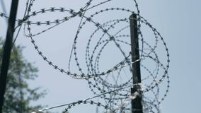 Barbed wire with cold sky. Barbed wire fence top. Close-up panorama stock video footage