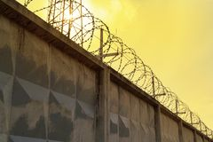 Barbed wire on a concrete fence against the background of a poisonous yellow sky stock images