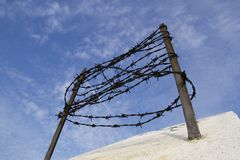 Barbed wire on the concrete fence against the blue sky. Captivity and deportation concept.  stock photography
