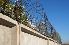 Barbed wire on a concrete fence Royalty Free Stock Photos