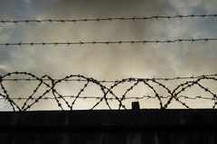 Barbed wire on dark fence. royalty free stock photos