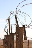 Barbed wire with decayed wood fence Royalty Free Stock Photo