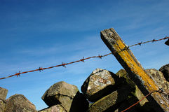 Barbed wire and a dry-stone wall Stock Photo