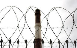 Barbed wire and factory pipe Stock Photography