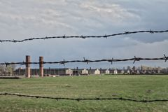 Barbed wire and fance around a concentration camp. Shed guard in the background. Stock Photo