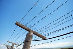 Barbed wire fence. Against blue sky background stock photos