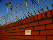 Barbed wire fence. On a wall Stock Image