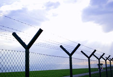 Barbed wire fence. Against cloudy sky and rays of light Stock Image