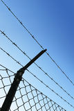 Barbed wire fence. Against blue sky Royalty Free Stock Photography