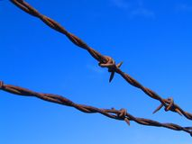 Barbed Wire Fence. A barbed wire fence against a flawless sky Royalty Free Stock Photography