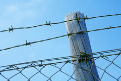 Barbed wire fence. Against blue sky Stock Photo