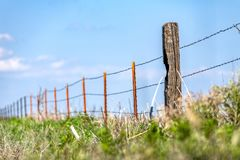 Barbed wire fence against blue sky Royalty Free Stock Photo