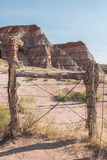 Barbed Wire Fence Along Desert Rocks Stock Photo