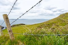A Barbed Wire Fence. Antrim/N. Ireland - May 30, 2015: The rolling hillside of Antrim with a post and barbed wire fence. Rathlin Island sits off in the distance royalty free stock images
