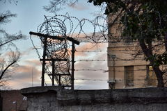 Barbed wire fence around prison walls Royalty Free Stock Photos