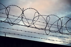 Barbed wire fence around prison walls Royalty Free Stock Images