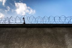 Barbed wire fence around prison walls, blue cloudy sky in background, security, crime illegal immigration concept. Barbed wire fence around prison walls, blue stock photo