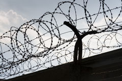 Barbed wire fence around prison walls blue sky. In background Stock Photo