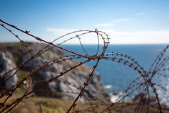 Barbed wire on fence with Atlantic ocean Royalty Free Stock Image