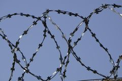 Barbed wire fence attached around prison walls.  Royalty Free Stock Photo