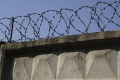 Barbed wire fence attached around prison walls.  Royalty Free Stock Images