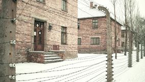 Barbed wire fence of Auschwitz Birkenau concentration camp. Old brick buildings in falling snow Stock Image