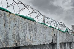 High security colony fenced with barbed wire for criminals with life imprisonment. Barbed wire fence birth enclosing the prison and places of detention for Stock Photos