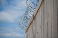 Barbed wire on a fence with blue sky. Barbed wire on a  wooden fence, prison, freedom outside this fence Stock Image