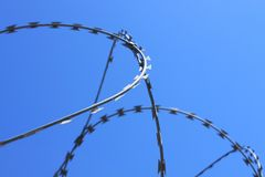 Barbed wire on fence with blue sky, the concept of prison, salvation, copy space. royalty free stock photos