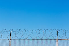 Barbed wire fence on blue sky Royalty Free Stock Images