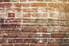 Barbed wire fence with brick wall. Royalty Free Stock Photos