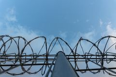 Barbed wire fence with bright blue sky to feel silent and lonely and want freedom. Dramatic clouds behind barbed wire fence on a stock photography