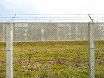 Barbed wire fence and cement wall Royalty Free Stock Images