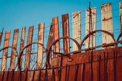 Barbed wire fence and chain fence with sharp sharp thorns rusty palisade against the blue sky Stock Photos