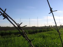 Barbed wire fence closeup of the antenna away royalty free stock photography