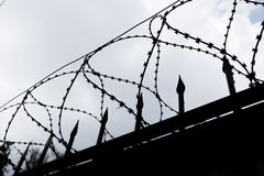 Barbed wire fence on a cloudy day stock photography