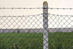 Barbed wire fence and column. In front of the factory Stock Images