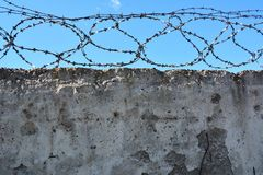 Barbed wire fence. Concrete wall, against the backdrop of barbed wire, the concep Royalty Free Stock Photo