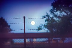 Barbed wire fence at the countryside ranch under the moon light, summer night stock photo