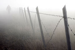 Barbed wire fence in dense fog Stock Image