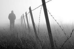 Barbed wire fence in dense fog Stock Images