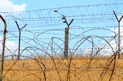 Barbed wire fence. In the desert against the blue sky Stock Photography