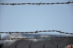 Barbed wire fence and horizon. Barbed wire fence in near foreground, with the haze of mountains and blue sky in the background royalty free stock photos