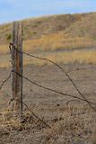 Barbed Wire and Fence Post with Wild Prairie Background Royalty Free Stock Image