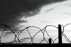 Barbed wire fence prison dark stock photo