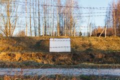 Barbed wire fence protects the danger zone. White sign board.  royalty free stock images