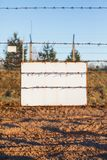 Barbed wire fence protects the danger zone. White sign board.  royalty free stock photos