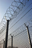 A barbed wire fence with razor sharp wires Stock Photo