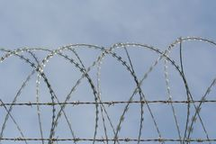 Barbed wire fence with razor wire. Barbed wire with razor wire Stock Image