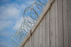 Barbed wire on a fence - Refugees. Barbed wire on a  wooden fence, prison, freedom outside this fence Royalty Free Stock Photography